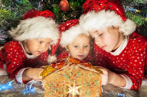 3 little girls building a gingerbread house